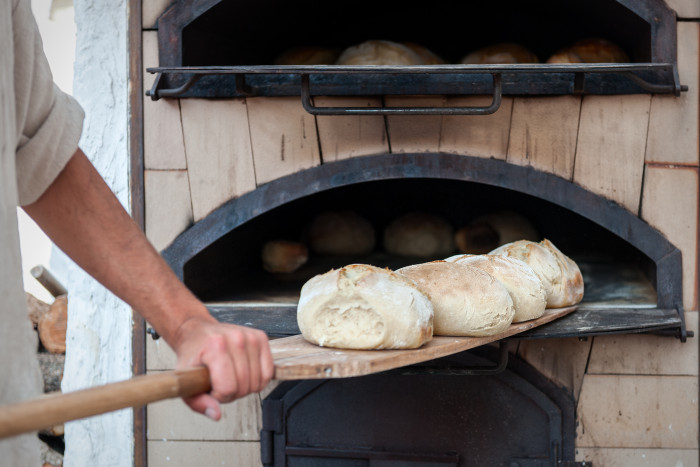 Baker using brick oven to bake bread.