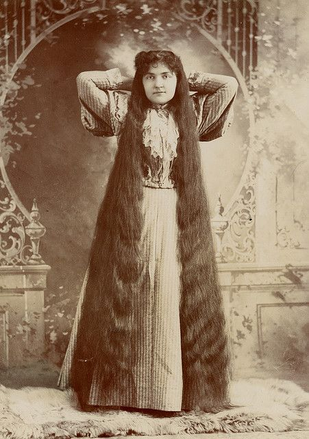 Kristin Holt | L-O-N-G Victorian Hair. Brunette with her hands behind her head, showing off her floor-length hair. By her dress, year is assumed to be mid 1890's. Image from Flicker and Pinterest.