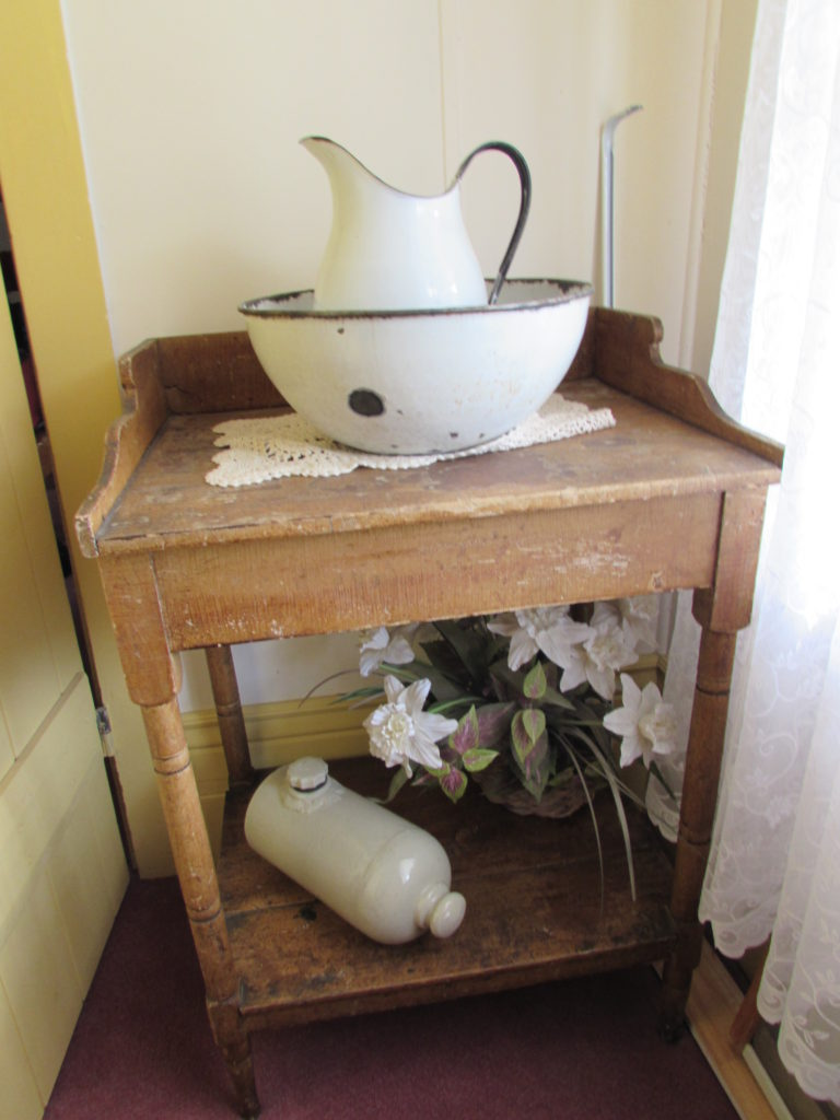 """Toilet"", a.k.a. wash stand with pitcher and bowl. On the bottom shelf, see the antique bed warmer. Historic Idaho Hotel, Silver City, Idaho."