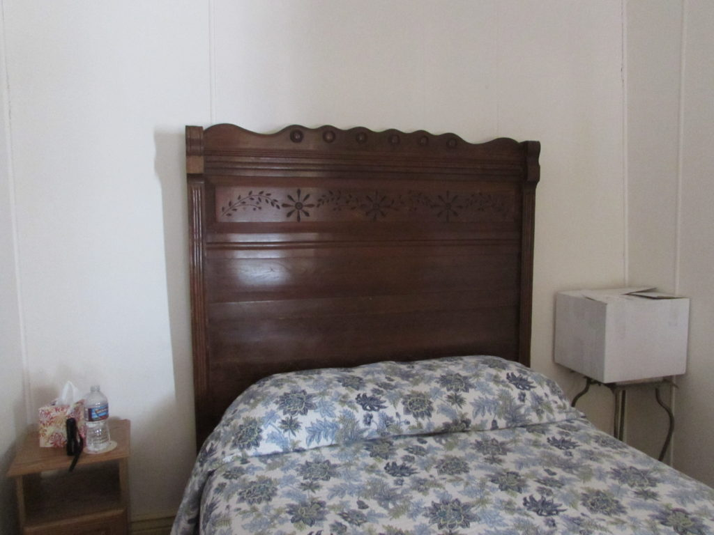 Historic Idaho Hotel, Room #8, antique headboard (and foot board, not pictured). The box on the bedside table belonged to a guest; not part of the exquisite furnishings.