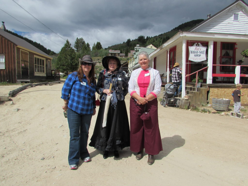 Authors: Ann Charles, Charlene Raddon, and Paty Jager, standing in the street [Washington Street, Silver City, Idaho] (photographer's back is to the hotel).