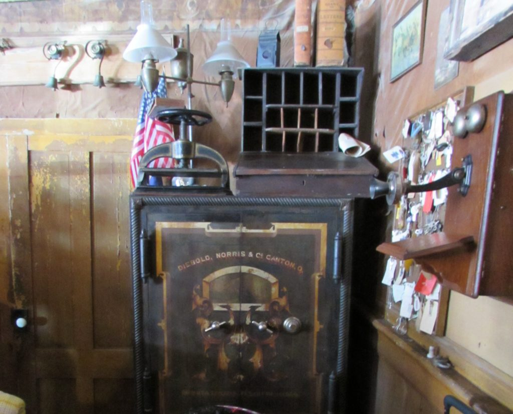 Antique safe behind the Check-In desk at Idaho Hotel, Silver City, Idaho. Note the bells above the door (top left), the vintage telephone (far right), and the writing desk (lap or tabletop use) on top of the safe. Vintage stationery from a prominent female guest had been found in the desk in this century. See the dual oil lamps and message boxes behind the lap desk (also on top of safe). The lobby is filled with antique treasures!