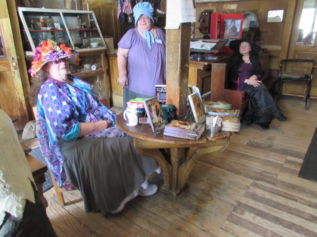 Jacquie Rogers (seated, left) at an unusual and clever antique table, built around a support beam in the lobby of historic Idaho Hotel (Silver City, Idaho). Jacquie Rogers held a book signing during her Much Ado About Silver City event in June, 2016.