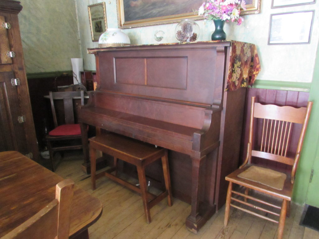 Antique Upright Grand Piano, in the dining room of historic Idaho Hotel, Silver City, Idaho.