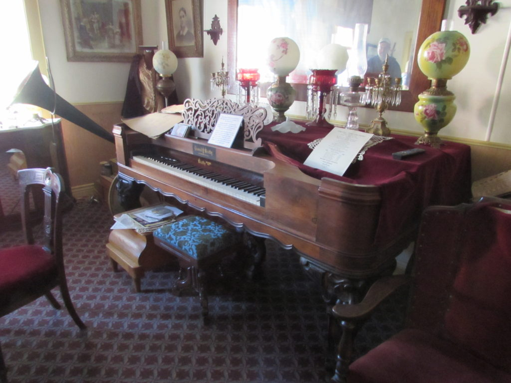 Antique piano and other decor in the Ladies' Parlor, a room generally closed to the public within the Historic Idaho Hotel, Silver City, Idaho.