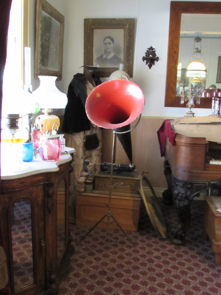 Edison Triumph Phonograph, on display in the Ladies' Parlor, historic Idaho Hotel of Silver City, Idaho. Note the rolls stacked on the wooden case.