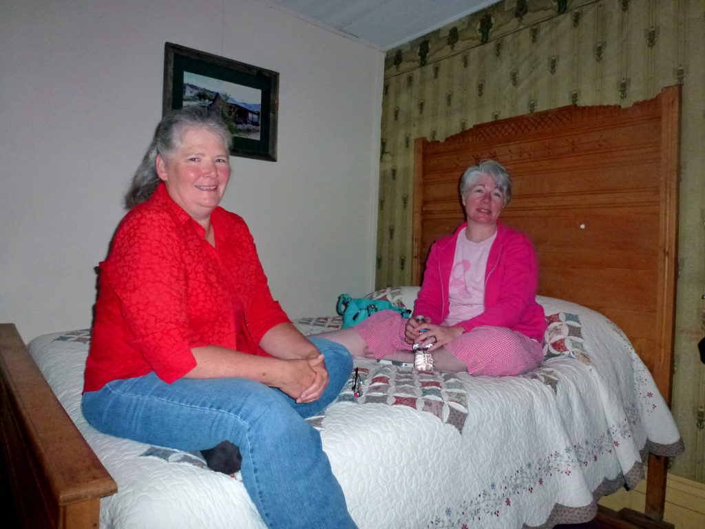 Authors Paty Jager (left) and Kristin Holt (right) visiting late one evening in Shirl Deems's room at the historic Idaho Hotel, Silver City, Idaho. Note the antique bed frame and vintage wallpaper. Image courtesy of Shirl Deems.