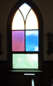 Colored glass windows along the sides of the historic Our Lady of Tears Catholic Church in Silver City, Idaho. Because of the nature of the building and climate (shifting and settling), the windows are frequently broken. Replacements are true to history.
