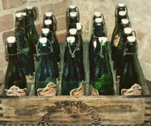 Kristin Holt | Victorian Americans Celebrate Oktoberfest. Green glass bottles with a mechanical stopper, in a vintage wooden carrying box.