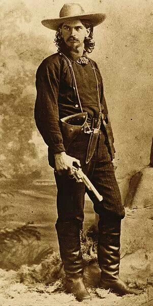 """Wild"" Ben Raymond, with .44 Merwin & Hulbert in one hand and a Smith & Wesson No. 3 New model in his holster. He wears a Bowie knife around his neck. He worked as a mine guard, posed for his photograph in Leadville, Colorado, in 1879, holding a First Model open top Merwin Hulbert Frontier Army revolver. Although the arm is believed to have been a photographer's prop, it nonetheless shows the Merwin's presence in the Wild West. Image: Courtesy of Pinterest."