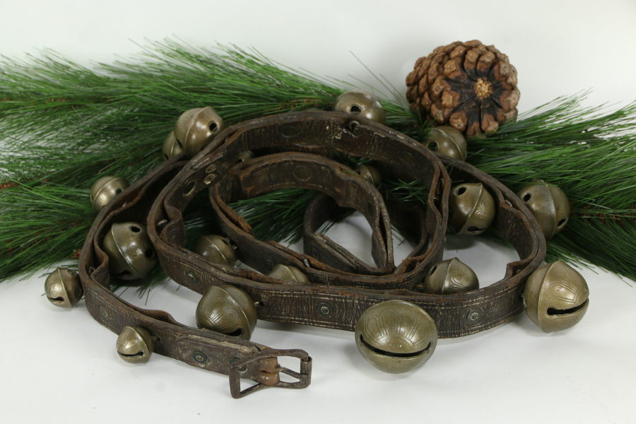 Kristin Holt | How to Conduct a Victorian Sleigh Ride. Photograph of Victorian Antique Brass Sleigh Bells mounted on an 88-inch leather harness belt that is 1.25-inches wide. Bells range from 1.25-inches to 2.25-inches. Sold by The Harp Gallery.