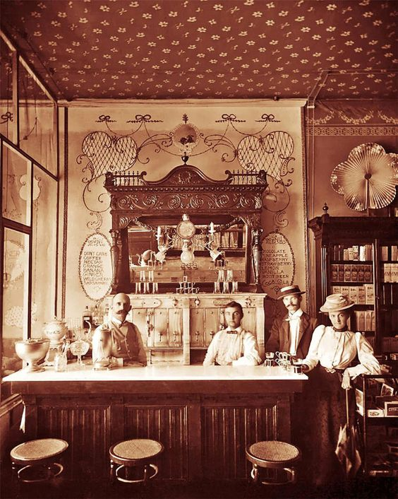 Kristin Holt | The Victorian-era Soda Fountain. Black and white vintage photograph: Soda fountain with soda men behind the bar. Image Courtesy of Pinterest.