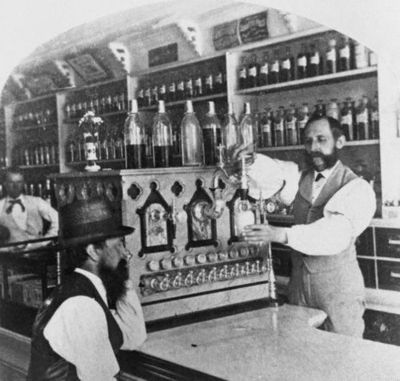 Kristin Holt | The Victorian-era Soda Fountain. Black and white vintage photograph: Worker pouring soda for a customer, circa 1890. Image Courtesy of Pinterest.