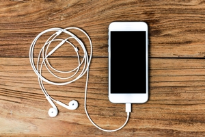 Kristin Holt | Book Review: Trio of Old West Tales. Photo of an iphone with connected earphones. Photo used by premium subscription agreement with Freepik.