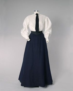 Kristin Holt | Image: photograph of 1902 Ladies' Fashion [ladies' white shirtwaist blouse with collar, mannish necktie (in navy blue) and walking shirt (A-line) in navy blue.]. Image from Pinterest.