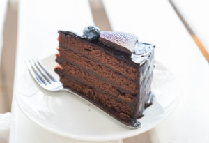 Kristin Holt | Victorian Baking: Devil's Food Cake ~ Image of chocolate fudge cake in cafe. Copyright listed, with photographer's name. Used from freepik's paid premium subscription.