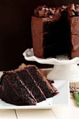 Kristin Holt | Victorian Baking: Devil's Food Cake ~ photograph of restaurant-style three-layer dark chocolate cake. Plated slice, with remaining cake on pedistal in background. Image copyright freepik; subscription use.