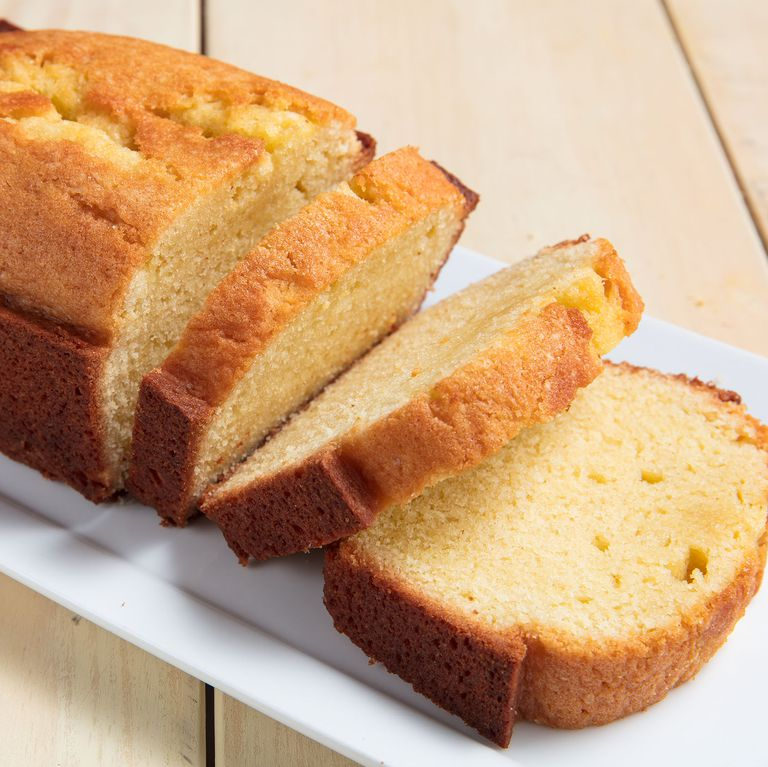 Photograph of a loaf Pound Cake cut into slices upon a serving plate. Photograph courtesy of Delish.com.