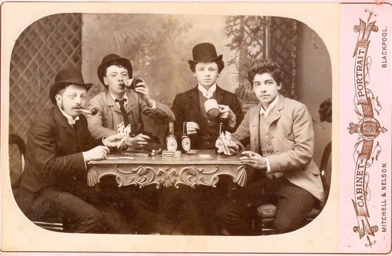 Antique cabinet card photograph of young men smoking, drinking, and gaming.